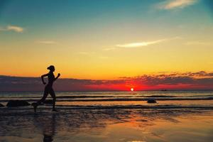 Frau läuft entlang der Seeküste foto