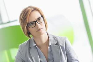 junge Geschäftsfrau, die weg im Büro schaut foto