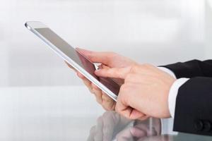 Geschäftsmann, der digitales Tablett am Schreibtisch hält foto