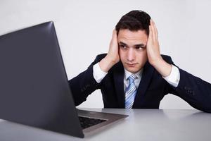 besorgter Geschäftsmann, der Laptop am Schreibtisch betrachtet foto