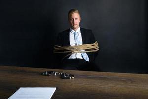 Geschäftsmann gebunden mit Seil, das vor Tisch sitzt