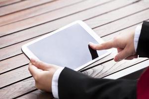 Geschäftsfrau, die digitales Tablett im Freien hält foto