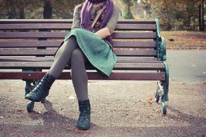 junge Frau, die auf einer Parkbank sitzt foto