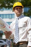 Architekt im Helm, der Blaupause auf Baustelle hält foto