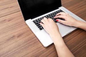 Nahaufnahme der Hände der Geschäftsfrau mit Laptop am Tisch