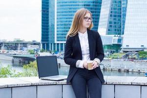 Frau auf Kaffeepause mit Laptop, der auf der Straße sitzt foto