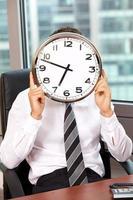 Geschäftsmann, der Uhr über Gesicht hält foto