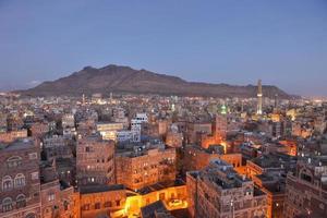 Stadtbild von Sanaa in der Abenddämmerung - traditionelle Jemenhäuser foto