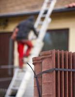 Arbeiter, der neue Dachziegel auf Haus setzt foto