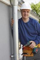 Arbeiter, der Dachrinne an der Außenseite des Hauses ersetzt foto