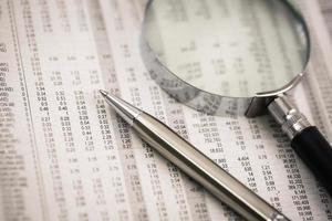 Kugelschreiber ruht auf Weltwährungszahlen foto