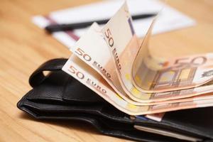 Haufen Euro-Banknoten auf einem Holztisch foto