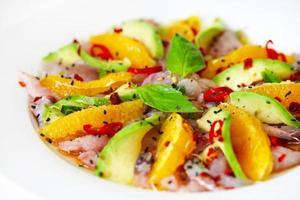 Rohes Fischsalat Carpaccio mit Avocado und Orangenscheiben foto