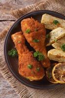 Hähnchenschenkel im Teig, mit Kartoffel auf Teller. Draufsicht foto