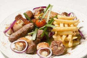 gegrilltes Fleisch und Pommes auf einem Teller foto