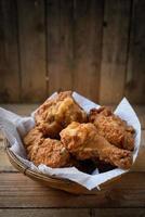 gebratenes Huhn in einem Korb auf einem Holzboden. foto