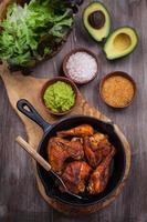 Gegrillte Hähnchenschenkel und Flügel mit Guacamole foto