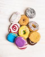 Haufen bunter Donuts auf weißem hölzernem Hintergrund, Draufsicht