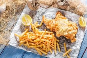 frischer Fisch und Chips in Papier serviert foto