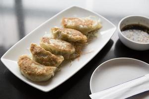 Jiaozi, chinesischer Knödel auf schwarzem Tisch mit Sauce