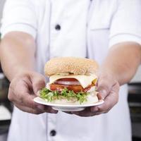 Nahaufnahme Chef präsentiert Hamburger foto