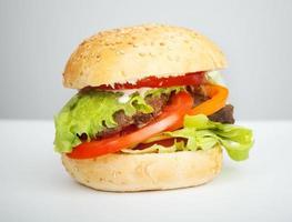 großer Hamburger liegt auf dem Tisch über grauem Hintergrund
