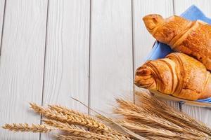 zwei Croissants und Weizenähren auf altem weißem Holz foto