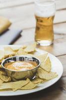 Nacho-Chips mit Käse und Bier foto