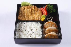 Bento-Set aus frittiertem Schweinefleisch (Tonkatsu), Gyoza, japanischem Reis foto