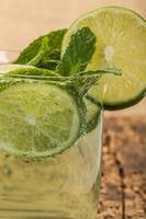 Erfrischungsgetränk mit Limette und Minze dekoriert