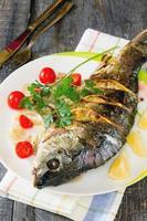 gebackener Fisch (Karpfen) mit Zwiebeln und Zitrone foto
