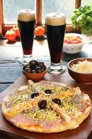Palmetto-Pizza mit zwei Gläsern Bier und Zutaten foto