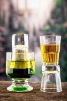 gelbgrüner Cocktail in einem Glas und Schuss