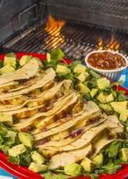 Gegrillte Hähnchen-Quesadias, serviert mit Koriandersalsa und Avacado-Chuncks foto