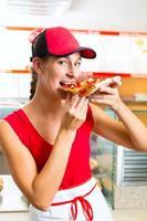 Frau, die ein Stück Pizza isst foto