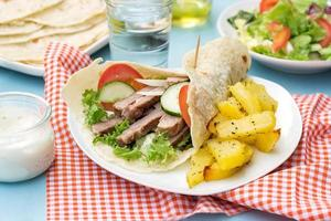 griechische Gyros mit Schweinefleisch, Gemüse und hausgemachtem Fladenbrot