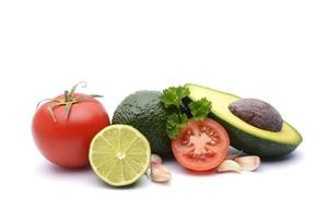 frische Avocado, umgeben von Tomaten, Knoblauch und Limette foto