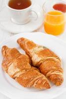 Croissant mit Tee, Saft und Marmelade