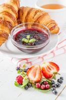 Frühstück - Croissants mit Straberry, Himbeere und Brombeere, Tee, Marmelade foto