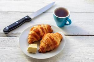 Frühstück mit frisch gebackenen Croissants, Butter und Kaffee
