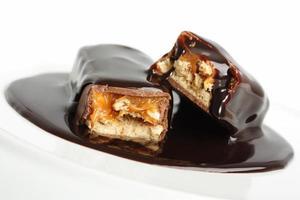 Gießen mit Schokoladensirup Schokoriegel foto