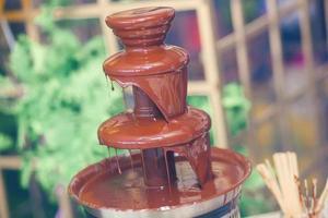 Schokoladenbrunnen mit Fondue, Früchten und Marshmallow auf Kinderparty foto