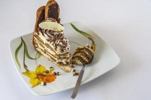 Tiramisu-Kuchen und Löffel auf einer Untertasse foto