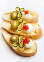 Bruschetta mit Mozzarella, grünen Oliven, Zucchini und rotem Kaviar foto