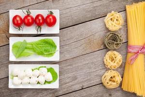 Tomaten, Mozzarella, Nudeln und grüne Salatblätter foto
