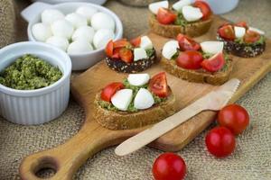Bruschetta mit frischen Tomaten, Mozzarella und Kräuterpesto foto