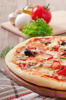 Pizza mit Schinken, Pilzen und Oliven foto