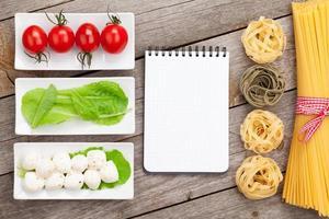 Tomaten, Mozzarella, Nudeln und grüne Salatblätter mit Notizblock