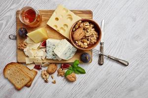 vier Käsesorten mit Nahrungsergänzungsmitteln, getrocknetes Brot, Feigen anderer weißer Tisch foto