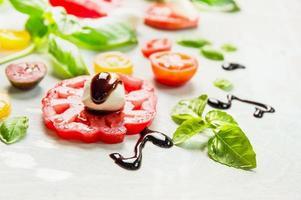 Tomatenscheibe mit Mozzarella und Basilikumblättern, Nahaufnahme foto